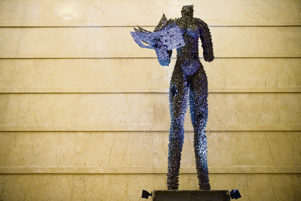 This picture shows a giant sculpture made with cartridges by the Congolese artist Freddy Tsimba, inaugurated at the Palais Chaillot, in Paris, on December 6, 2018 as part of  the 70th anniversary of the Declaration of Human Rights. - The spectacular 4.25 meters statue represents a woman from Democratic Republic of Congo walking. Gaping holes in one leg, the belly recall the abuses of which women in particular are victims. (Photo by Eric FEFERBERG / AFP) / RESTRICTED TO EDITORIAL USE - MANDATORY MENTION OF FREDDY TSIMBA UPON PUBLICATION - TO ILLUSTRATE THE EVENT AS SPECIFIED IN THE CAPTION